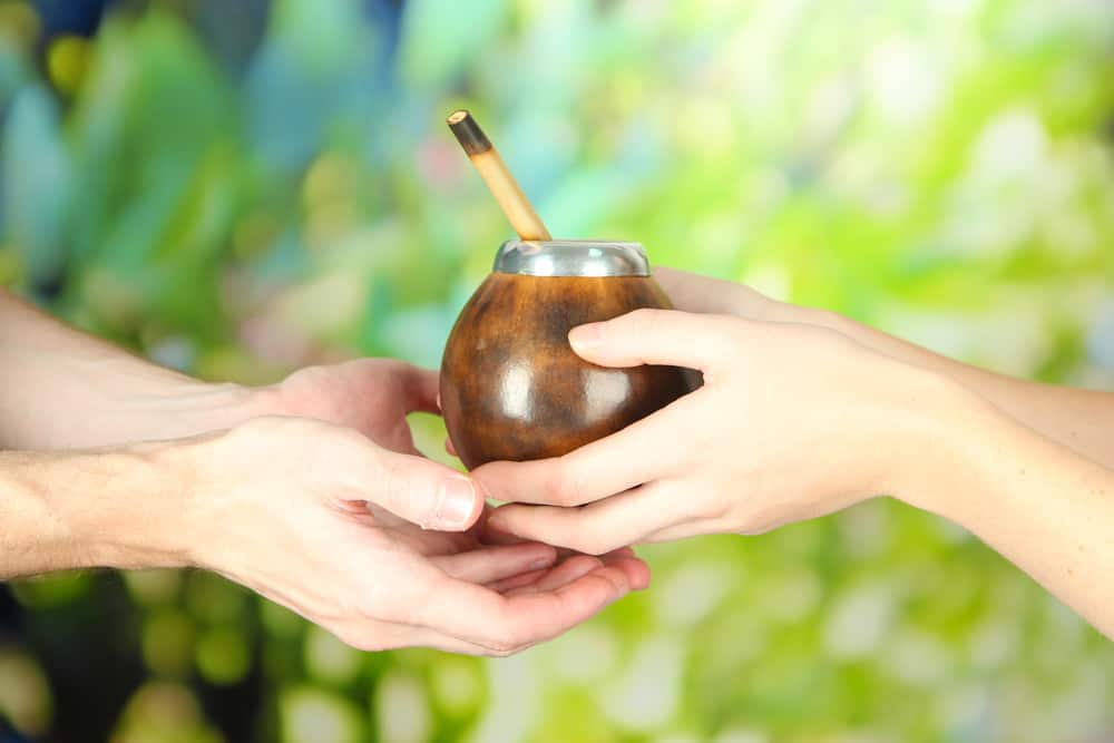 two hands sharing a gourd of yerba mate