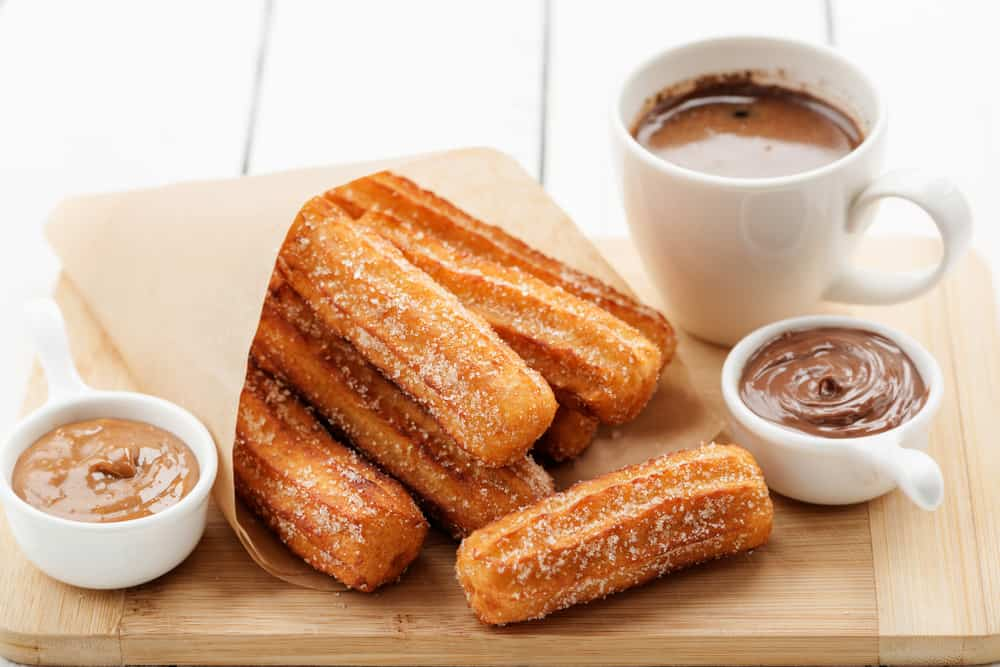 Churros in a bag with chocolate dipping sauce and coffee