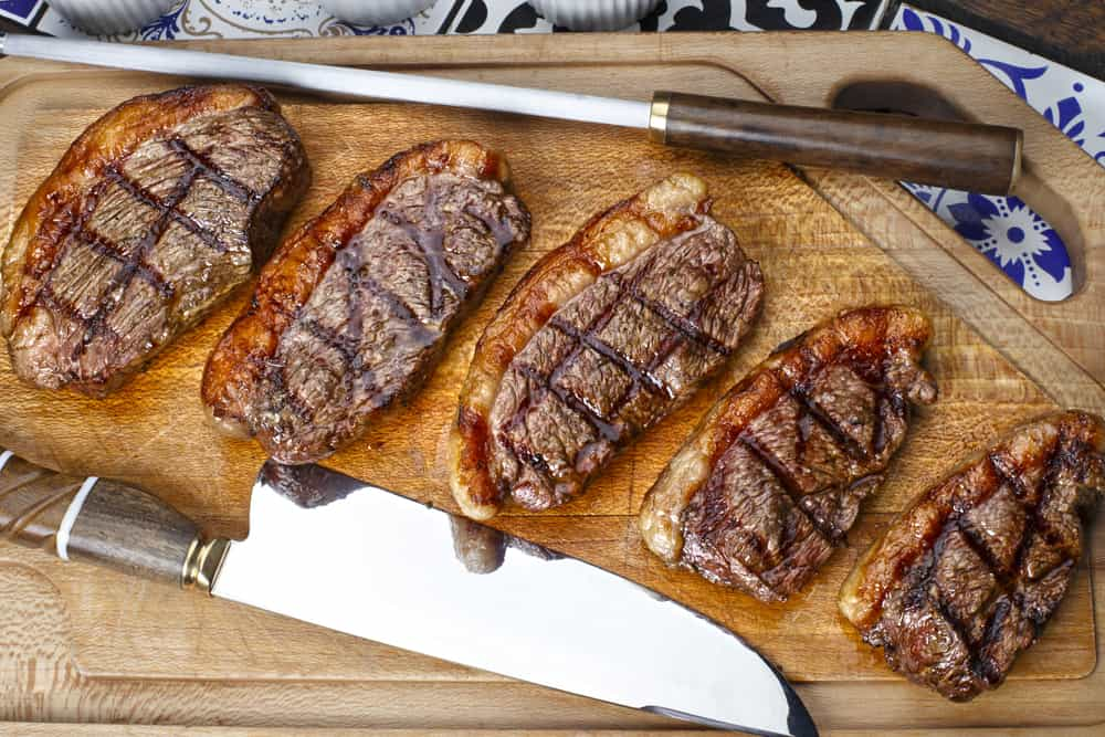 Picanha Brazilian steaks and cutting knife on cutting board