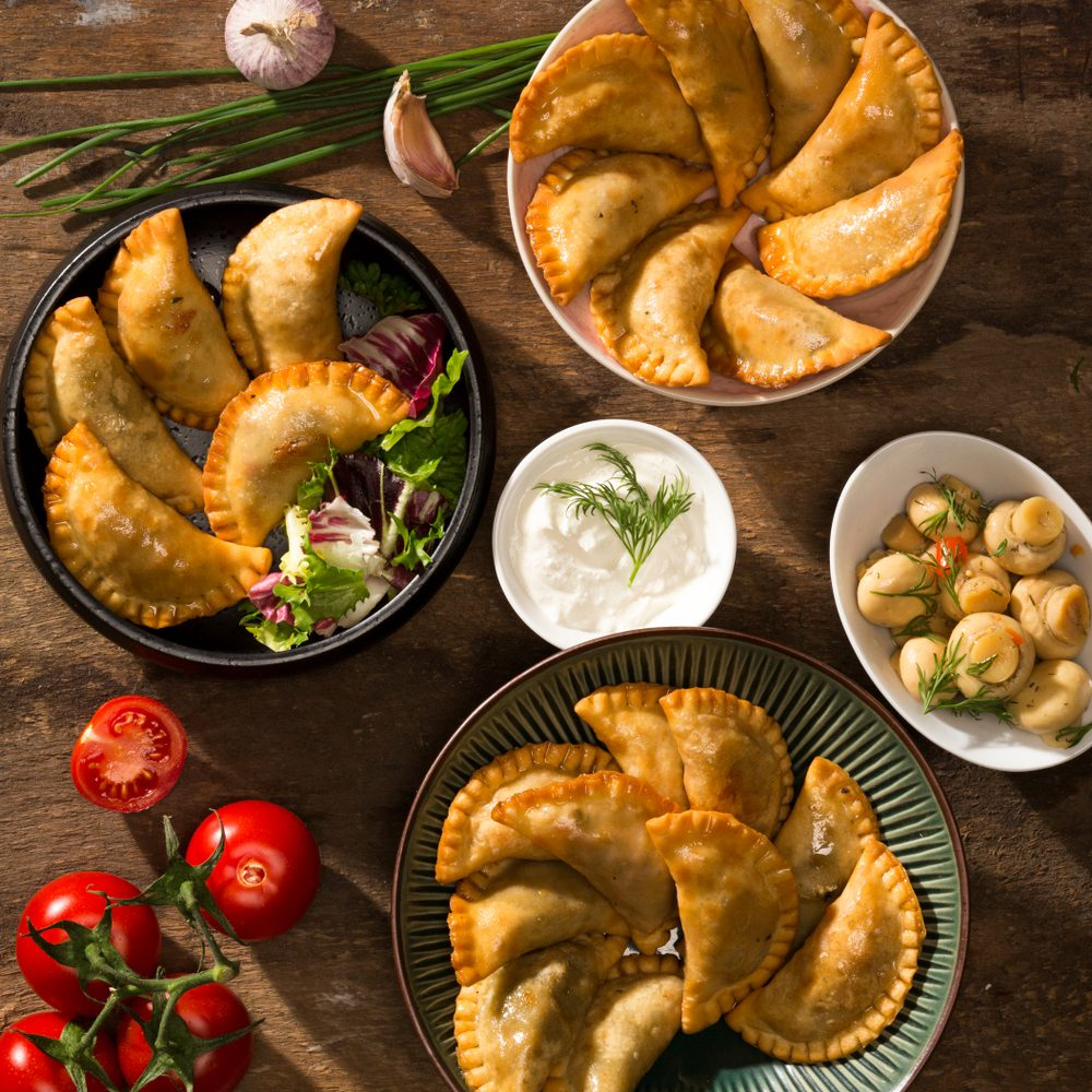 Assorted empanadas in bowls with sauces