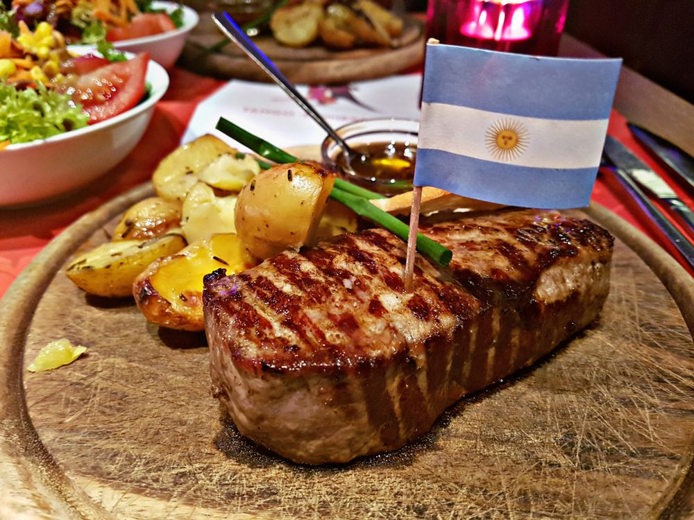 Cut of Argentinian steak with flag of Argentina stuck in iy on wooden table with vegetables in the background
