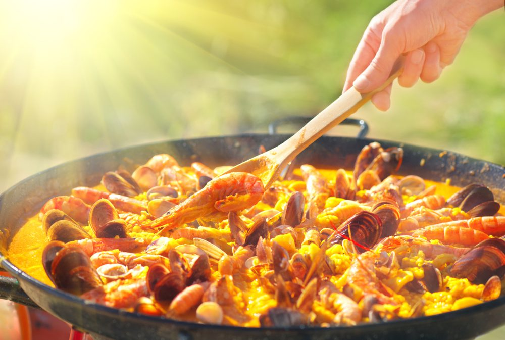 paellaera cooking of Spanish paella and wooden spoon