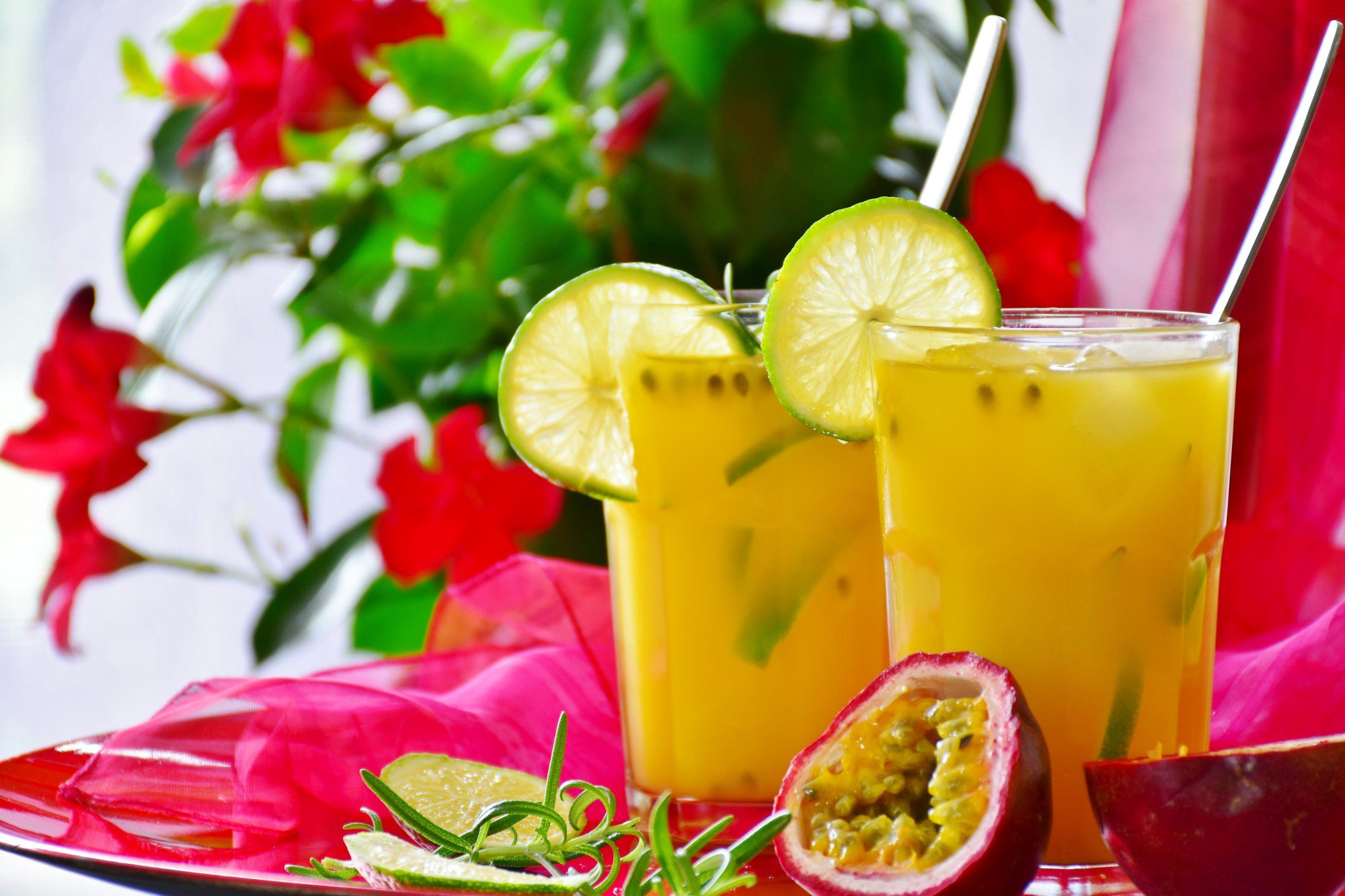Two glasses of passion fruit drinks with lime an straws