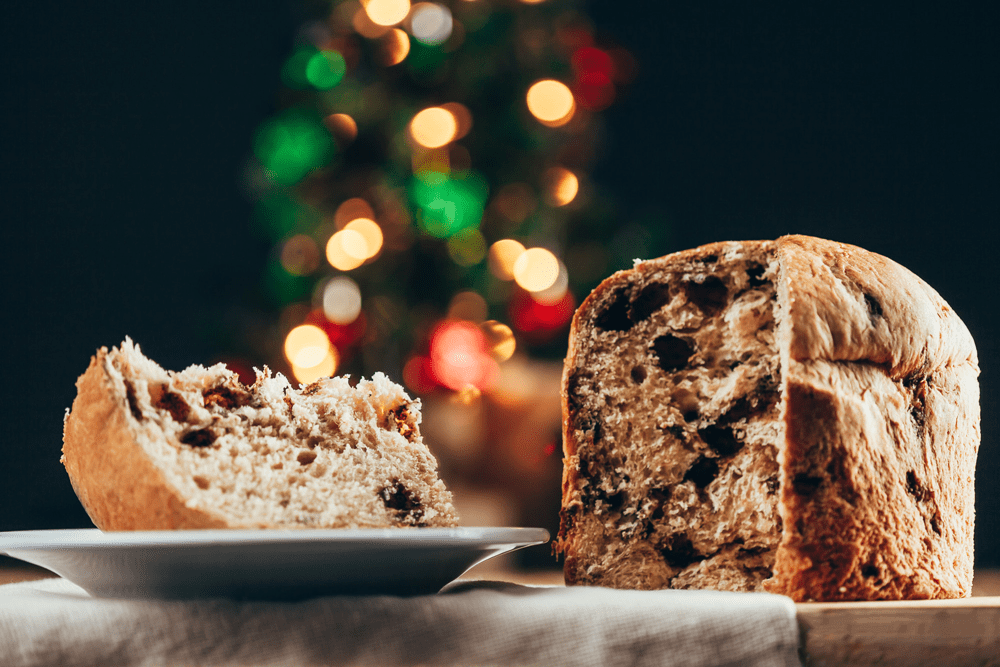 Brazilian panettone sliced with Christmas lights background