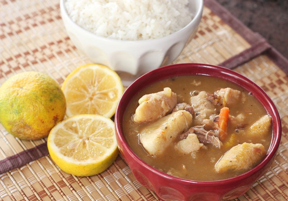 Dominican sancocho served in a bowl with a bowl of white rice and sliced lemons on a table