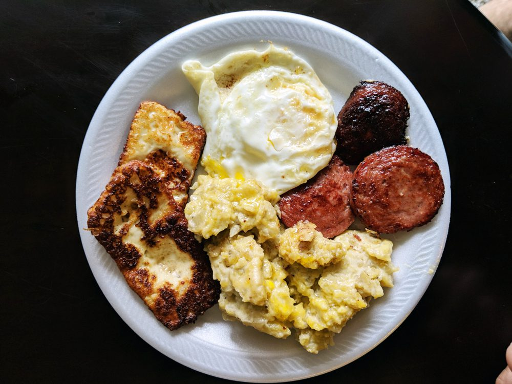 Dominican mangu, fried eggs, fried cheese and Dominican salami on white plate.