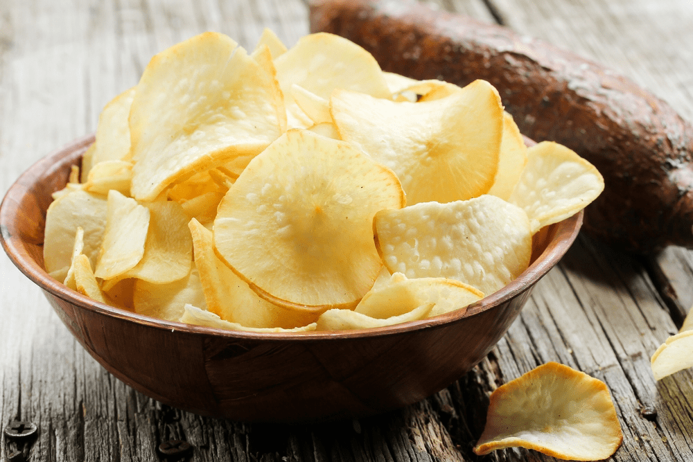 Yuva chips in a brown bowl with a yuca in the background