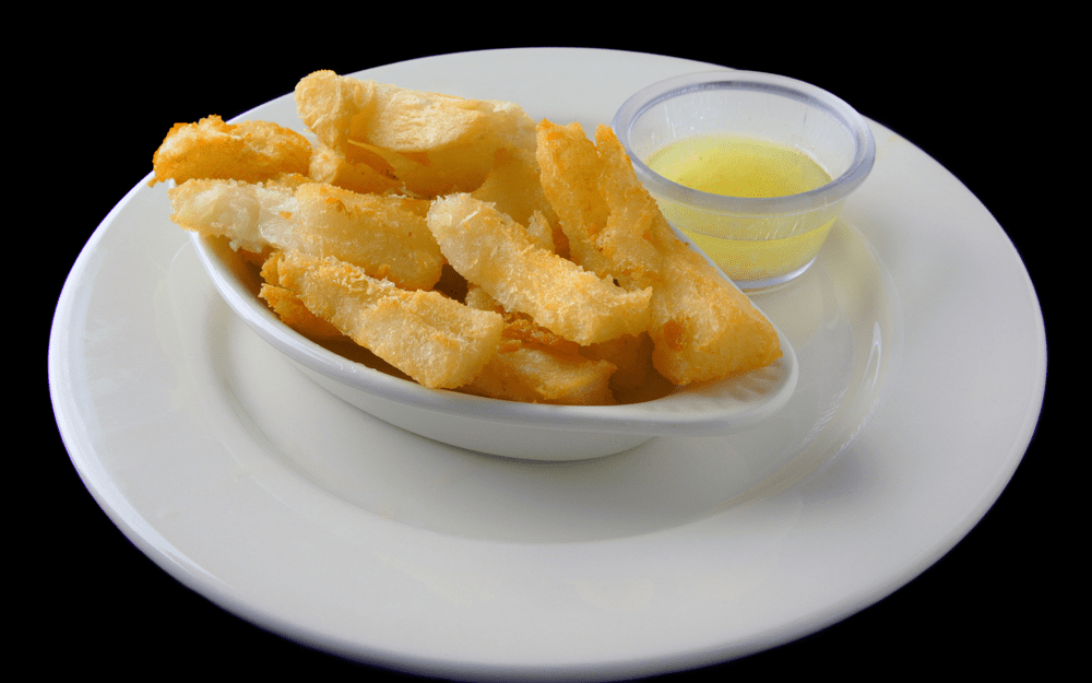 Yuca Fries on a white plate with mojo dipping sauce