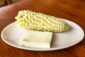 Choclo corn with Peruvian cheese on a white plate