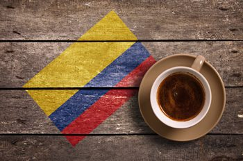 Colombian flag with cup of coffee on wooden table