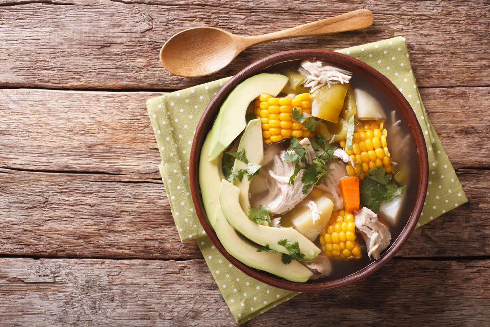 Bowl of ajiaco Colombian Cuisine on wooden table with spoon
