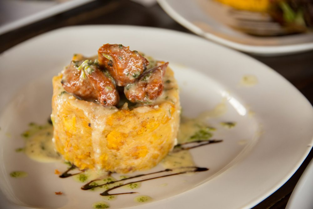 Plate of Puerto Rican Monfongo topped with meat served on white plate