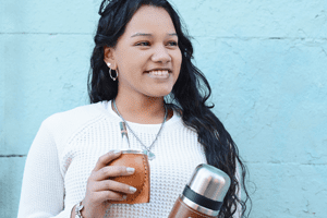 Woman holding yerba mate gourd and yerba mate thermos