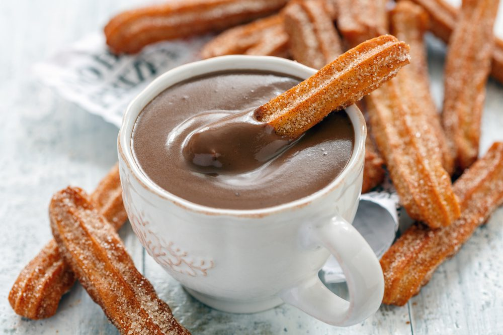 Spanish Christmas Churros with a white cup of hot chocolate