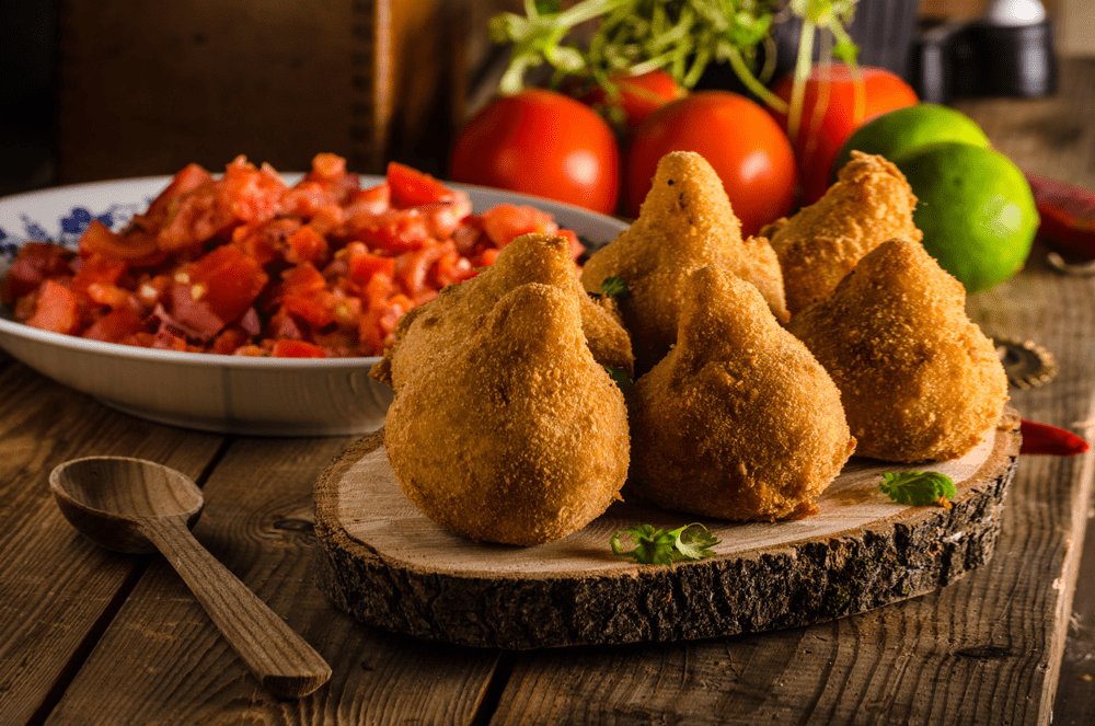 Plate of Brazilian Coxinha ant tomatoes in background