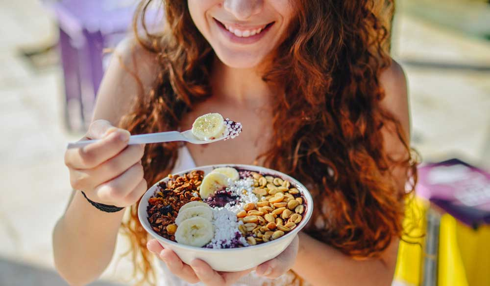 Woman eating bowl of acai and other fruits and granola